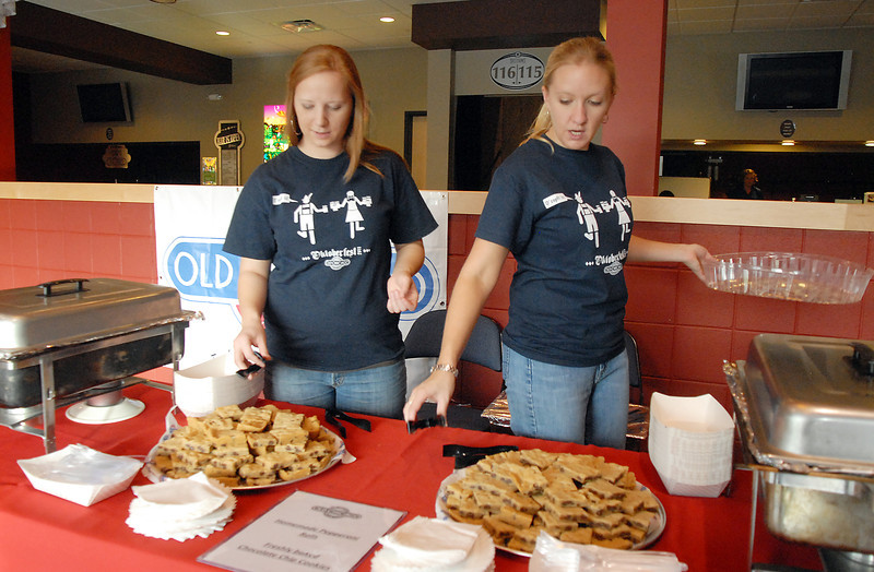 Tricia Tolar, left, and Jess Spillman prepare to serve food at the Old Chicago booth at Dancing With The Broomfield Stars at the 1stBank Center on Wednesday.<br /> September 22, 2011<br /> staff photo/ David R. Jennings