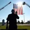 Battalion Chief Bruce Gunther talks on the radio to firefighters hanging the large U.S. flag between two fire tower trucks before the 9/11 Commemorative Ceremony at the 9/11 Memorial in Community Park.<br /> September 11, 2011<br /> staff photo/ David R. Jennings