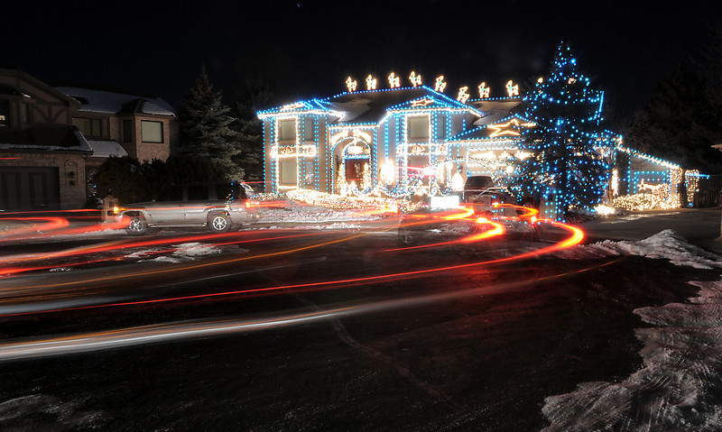 Vehicle lights shine as people look at the holiday lighting display at 13941 Tincup Circle nicknamed the Christmas House.<br /> <br /> December 9, 2011<br /> Staff photo/ David R. Jennings