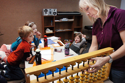 Dana Paige, right, uses a large abacus to help Tanner Simpson, 6, left, Kathryn Proctor, 7, and Riley MacQueen, 6, during abacus math class at the Davinci Center for Creative Arts on Wednesday. January 5, 2011 staff photo/David R. Jennings