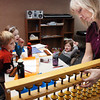 Dana Paige, right, uses a large abacus to help Tanner Simpson, 6, left, Kathryn Proctor, 7, and Riley MacQueen, 6, during abacus math class at the Davinci Center for Creative Arts on Wednesday.<br /> January 5, 2011<br /> staff photo/David R. Jennings