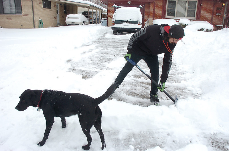 "Jose Gisi, with the ""supervision"" of his dog Aspen, shovels snow from his driveway on Emerald St. during the late December snow storm on Thursday <br /> <br /> December 22, 2011<br /> staff photo/ David R. Jennings"