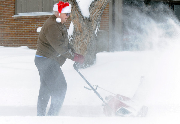 Jim Hahn, wearing a Santa hat,  uses his snow blower to help clear his neighbor's sidewalks a driveways during the late December snowstorm on Thursday.  Hahn cleared 5 driveways on Thursday morning.<br /> <br /> December 22, 2011<br /> staff photo/ David R. Jennings
