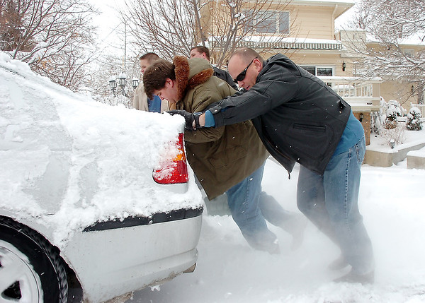 Dallas Scholes, right, with his sons Steven, 19, center, Tyler, 18, left, and Jed 14, push a neighbor's car that was stuck on East Holly Dr. during the December snow storm on Thursday.<br /> <br /> December 22, 2011<br /> staff photo/ David R. Jennings