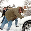 Steven Scholes, 19, right, with his brother Tyler, 18, left, help push and shovel out a neighbor's car that was stuck on East Holly Dr. during the December snow storm on Thursday.<br /> <br /> December 22, 2011<br /> staff photo/ David R. Jennings
