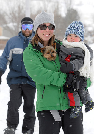 Theresa Rhodes carries her son Isaac, 1, and dog Penny walk along Oak Circle after trying to sled in the snow with her husband Phil during the late December snowstorm on Thursday. <br /> <br /> December 22, 2011<br /> staff photo/ David R. Jennings