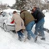 Dallas Scholes, right, with his sons Jed 14, Steven, 19, and Tyler, 18, far right, push a neighbor's car that was stuck on East Holly Dr. during the December snow storm on Thursday.<br /> <br /> December 22, 2011<br /> staff photo/ David R. Jennings