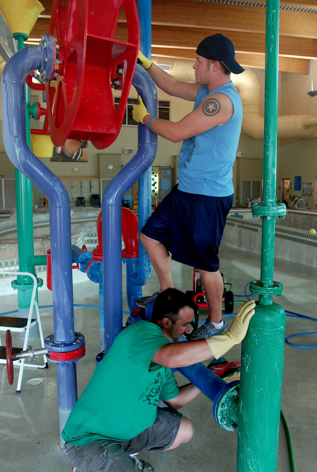 Shane Mortensen, above, and Andy Larington clean the water wheel in the pool during cleaning week at the Derda Recreation Center on Tuesday. <br /> August 24, 2010<br /> staff photo/David R. Jennings