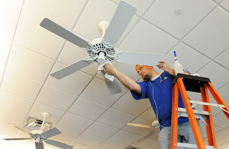 Matt Gulley cleans ceiling fans in an exercise area during cleaning week at the Derda Recreation Center on Tuesday. <br /> August 24, 2010<br /> staff photo/David R. Jennings