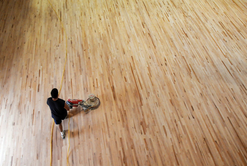 A worker with All City Hardwood sands the new gym floor during cleaning week at the Derda Recreation Center on Tuesday. <br /> August 24, 2010<br /> staff photo/David R. Jennings