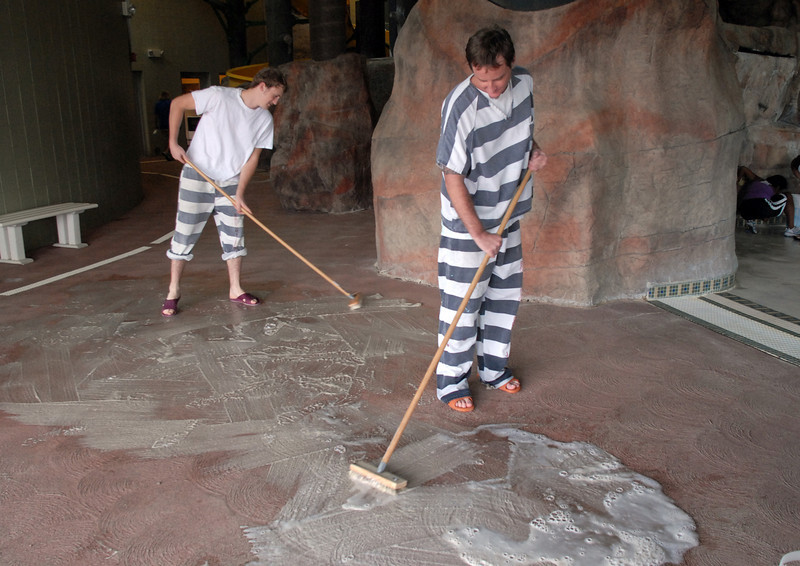 Broomfield County Jail prisoners Matthew Brooks, left, and Dustin Carara, clean the pool deck during cleaning week at the Derda Recreation Center on Tuesday. <br /> August 24, 2010<br /> staff photo/David R. Jennings