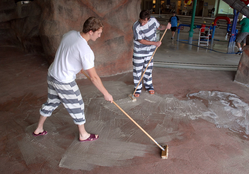BE0826DERDA05<br /> Matthew Brooks, left, and Dustin Carara, Broomfield County Jail prisoners clean the pool deck during cleaning week at the Derda Recreation Center on Tuesday. <br /> August 24, 2010<br /> staff photo/David R. Jennings