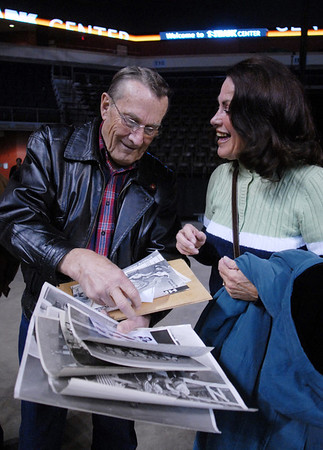 Roller Derby veterans Joe Weinmeier, left,  shows Cindy (McCoy) O'Neill photos from his days of skating in the roller derby during Saturday's first Denver Roller Dolls bout at the 1stBank Center. Weinmeier skated in the 1940's and 50's and McCoy skated in the 1960's.<br /> <br /> March 20, 2010<br /> Staff photo/David R. Jennings