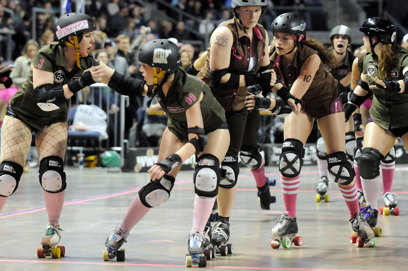 Denver Roller Dolls teams Green Barrettes, left, and Shotgun Betties move into position during Saturday's first bout at the 1stBank Center in Broomfield. <br /> <br /> March 20, 2010<br /> Staff photo/David R. Jennings