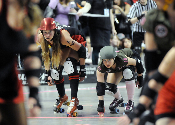 "Jammers Fonda Payne, left,  Bad Apples, and Julie ""Angela Death"" Adams, Green Barrettes, prepare for their sprint to begin the jam during Saturday's first Denver Roller Dolls bout at the 1stBank Center.<br /> March 20, 2010<br /> Staff photo/David R. Jennings"