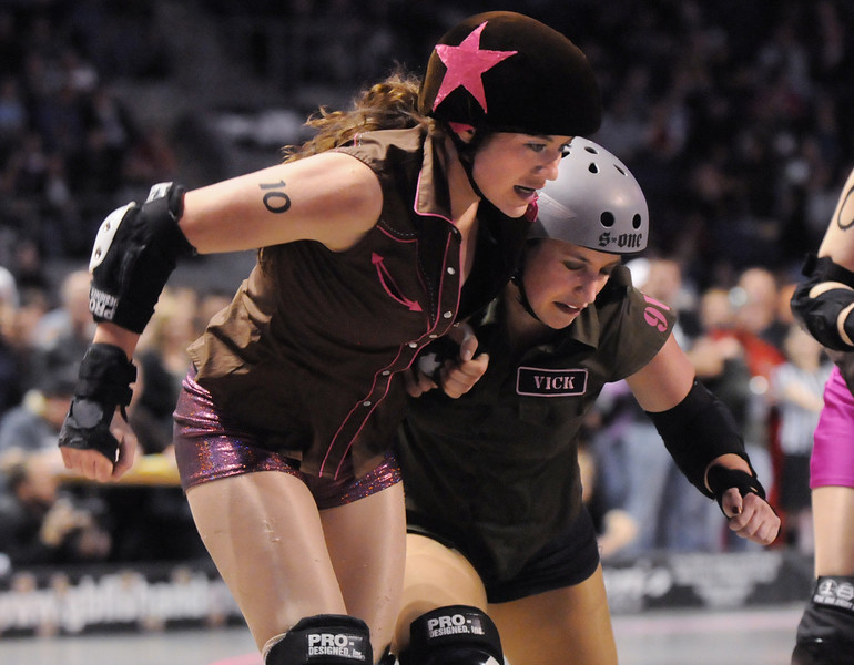 """Danica """"Berlin Brawl"""" Dolezal, left, Shotgun Betties is blocked by Vicky """"Slick Vick"""" Cruz, Green Barrettes during Saturday's first Denver Roller Dolls bout at the 1stBank Center. <br /> <br /> March 20, 2010<br /> Staff photo/David R. Jennings"""