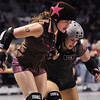 "Danica ""Berlin Brawl"" Dolezal, left, Shotgun Betties is blocked by Vicky ""Slick Vick"" Cruz, Green Barrettes during Saturday's first Denver Roller Dolls bout at the 1stBank Center. <br /> <br /> March 20, 2010<br /> Staff photo/David R. Jennings"