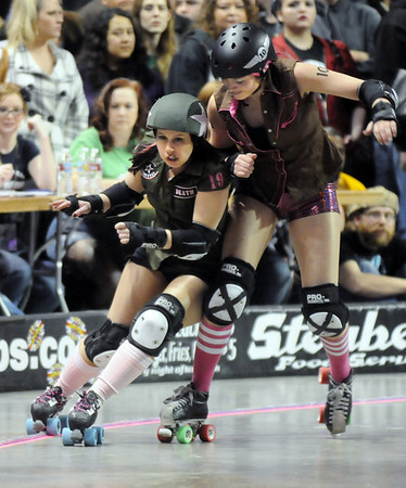 "Julie "" Angela Death"" Adams, left, Green Barrettes is knocked off the course by Danica ""Berlin Brawl"" Dolezal, Shotgun Betties during Saturday's first Denver Roller Dolls bout at the 1stBank Center.<br /> March 20, 2010<br /> Staff photo/David R. Jennings"