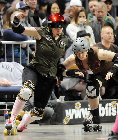Honey Punches of Throats , left, Green Barrettes is blocked off the course by Shannon Ball, Shotgun Betties during Saturday's first Denver Roller Dolls bout at the 1stBank Center. <br /> <br /> March 20, 2010<br /> Staff photo/David R. Jennings