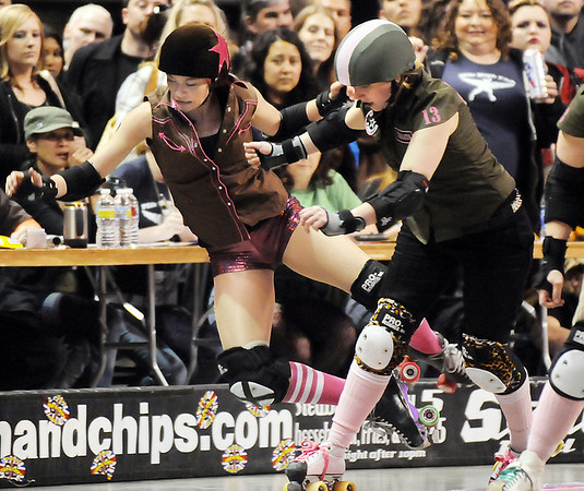 "Danica ""Berlin Brawl"" Dolezal, left, Shotgun Betties is knocked off the course by Honey Punches of Throats, Green Barrettes during Saturday's first Denver Roller Dolls bout at the 1stBank Center.<br /> March 20, 2010<br /> Staff photo/David R. Jennings"