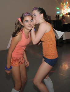 Megan Moore, 14, left, listens to a whisper by Melissa Learish, 14,  during the disco dance off for the School of Ballet Nouveau Colorado at the BNC studio on Saturday. July 9, 2011 staff photo/ David R. Jennings