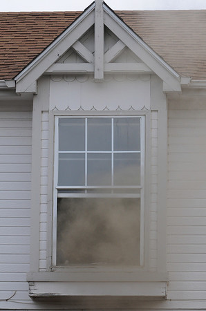 Smoke pours out of a second story window as North Metro Fire Rescue District firefightersextinguish the fire at 308 Mulberry Circle which caught on fire Saturday. No reports of injuries and the cause of the fire is under investigation.<br /> <br /> March 6, 2010<br /> Staff photo/David R. Jennings