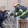 Broomfield Police commander Linda Haines takes a dog from North Metro Fire Rescue Capt. Rich Randall rescued by firefighters at a house fire at 308 Mulberry Circle on Saturday.<br /> No reports of injuries the cause of the fire  is under investigation.<br /> March 6, 2010<br /> Staff photo/David R. Jennings