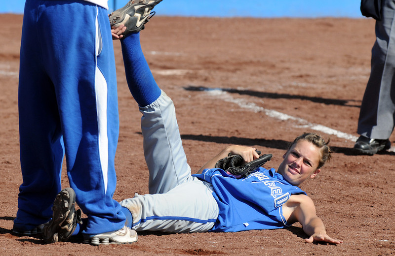 Sarah Fabrizio, Broomfield, gets help from a coach to stretch between innings during play against Longmont at Broomfield High Saturday.<br /> <br /> Sept. 26, 2009<br /> Staff photo/David R. Jennings