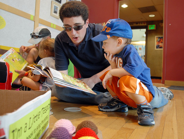 Bryan Antman sings a story to his son Jonah, 2 1/2,during the Early Literacy Fair at the Mamie Doud Eisenhower Public Library on Saturday.<br /> <br /> July 15, 2011<br /> staff photo/ David R. Jennings