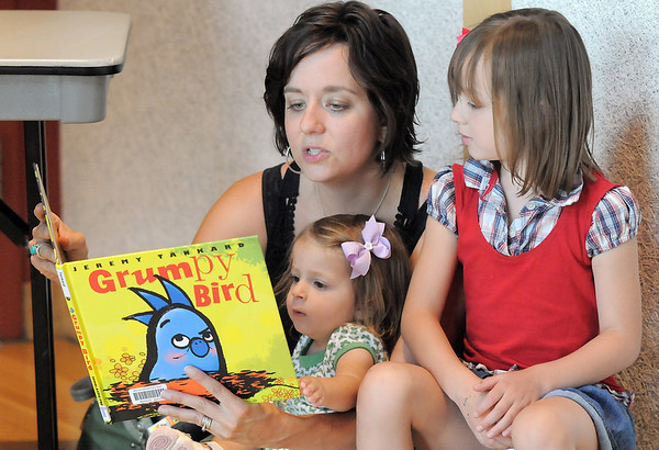 Christa Romig-Leavitt reads to her daughters Dayli, 19 months-old, and Stella, 5, during the Early Literacy Fair at the Mamie Doud Eisenhower Public Library on Saturday.<br /> <br /> July 15, 2011<br /> staff photo/ David R. Jennings