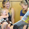 Adrienn Hollonds and her daughter Kinley, 2 1/2, read a book with Amy Tabor and her son Cody, 2 1/2, during the Early Literacy Fair at the Mamie Doud Eisenhower Public Library on Saturday.<br /> <br /> July 15, 2011<br /> staff photo/ David R. Jennings