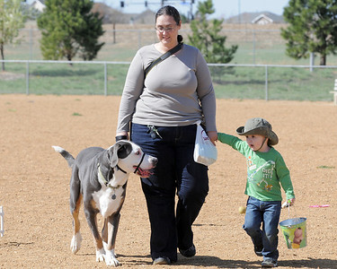 Ann Daniel, center, walks with Mojo, left, and her son Xander, 2, after the Paws in the Park egg hunt and Easter bonnet parade at the Broomfield County Commons Dog Park on Saturday. April 7, 2012  staff photo/ David R. Jennings