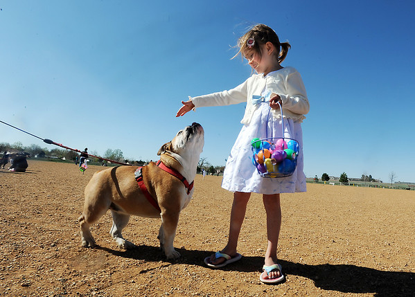 Riley Dowdel, 6 1/2, right, pets her English Bull Dog, Maddy, after the Paws in the Park egg hunt and Easter bonnet parade at the Broomfield County Commons Dog Park on Saturday.<br /> April 7, 2012 <br /> staff photo/ David R. Jennings