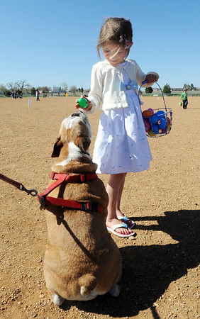 Riley Dowdel, 6 1/2, right, shows her English Bull Dog, Maddy, a plastic egg filled with a dog treat after the Paws in the Park egg hunt and Easter bonnet parade at the Broomfield County Commons Dog Park on Saturday.<br /> April 7, 2012 <br /> staff photo/ David R. Jennings