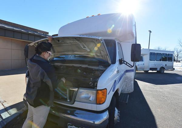 Easy Ride driver Monica Verdin checks fluids in her bus before shuttling seniors at the Broomfield Senior Center on Friday.<br /> January 4, 2013<br /> staff photo/ David R. Jennings