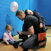 Colin Heintz puts shoes on his daughter, Zenna, 2, while his son Kolten, 5, takes a rest on his father's back during the Eggstravaganza Egg Scramble at the Broomfield Community Center on Saturday.<br /> <br /> April 23, 2011<br /> staff photo/David R. Jennings