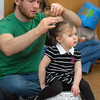 Zach Chavez adjusts the hair of his daughter, Athena, 2, using her Easter basekt for a chair before the start of the 0-2 year old session during the Eggstravaganza Egg Scramble at the Broomfield Community Center on Saturday.<br /> <br /> April 23, 2011<br /> staff photo/David R. Jennings