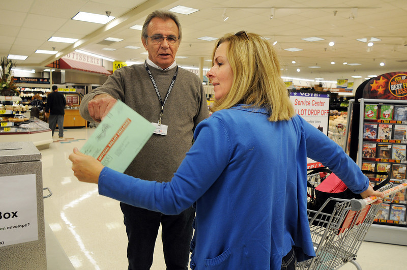 Election judge Paul LeGron  checks with Lisa Gyger if her ballot was signed before Gyger drops the ballot in the box and continues shopping at the Miramonte King Soopers on Tuesday. <br /> November 3, 2009<br /> Staff photo/David R. Jennings