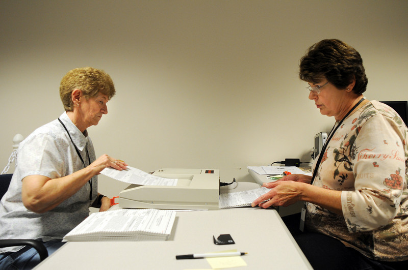 Jean Benaglio, left, and Charlotte Atencio put ballots through a vote counting machine at the City and County of Broomfield building on Tuesday.<br /> November 3, 2009<br /> Staff photo/David R. Jennings