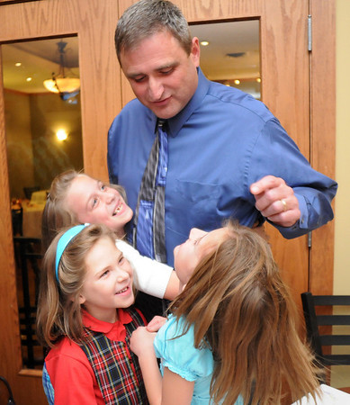 Broomfield council candidate Greg Stokes is hugged by his daughter Abby Stokes, 9, left, with her  friends Aex Neece, 6, and Lyndsey Hranicka, 9, during the election night party at Eagle Trace Golf Course on Tuesday.<br /> November 3, 2009<br /> Staff photo/David R. Jennings