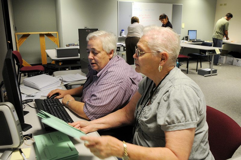 Phyllis Lorimer, left, and Elenore Bergstresser verify voter signatures on ballot envelopes before counting the ballots  in the basement of the City and County of Broomfield building on Tuesday.<br /> November 3, 2009<br /> Staff photo/David R. Jennings