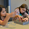 Mykaela Ryan, 11, left, and Rachel Halperin, 10, connect wires to light an LED bulb during the Electronic Lab taught by Fred Gluck of CU Science Discovery at Mamie Doud Eisenhower Public Library on Saturday.<br /> February 16, 2013<br /> staff photo/ David R. Jennings