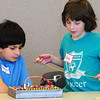 Daniyal Djalilzadeh, 10, left, and Cole Wiley, 9, connect a wire to the circuit board during the Electronic Lab taught by Fred Gluck of CU Science Discovery at Mamie Doud Eisenhower Public Library on Saturday.<br /> February 16, 2013<br /> staff photo/ David R. Jennings