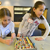Emily Allen, 10, left, and Catherine Carmosino, 9, right, looks over at neighboring team's work while trying to figure out how to correctly wire a switch on the circuit board during the Electronic Lab taught by Fred Gluck of CU Science Discovery at Mamie Doud Eisenhower Public Library on Saturday.<br /> February 16, 2013<br /> staff photo/ David R. Jennings