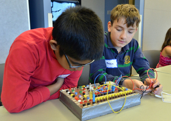 Kokila Gunasinghe, 9, left, and MaximTuell, 11, check if a light on the circuit board lights up during the Electronic Lab taught by Fred Gluck of CU Science Discovery at Mamie Doud Eisenhower Public Library on Saturday.<br /> February 16, 2013<br /> staff photo/ David R. Jennings
