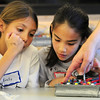Emily Allen , 10, left, and Catherine Carmosino, 9, get a hint from Jim Morgan on a wiring configuration on their board for an experiment during the Electronic Lab taught by Fred Gluck of CU Science Discovery at Mamie Doud Eisenhower Public Library on Saturday.<br /> February 16, 2013<br /> staff photo/ David R. Jennings