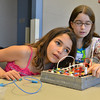 Mykaela Ryan, 101, left,  with Rachel Halperin, 10, listens for a faint tone from a buzzer on the circuit board during the Electronic Lab taught by Fred Gluck of CU Science Discovery at Mamie Doud Eisenhower Public Library on Saturday.<br /> February 16, 2013<br /> staff photo/ David R. Jennings