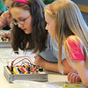 Gabrielle Green, 12, left, and Grace Braddock, 11, look for a lit LED bulb on the board during the Electronic Lab taught by Fred Gluck of CU Science Discovery at Mamie Doud Eisenhower Public Library on Saturday.<br /> February 16, 2013<br /> staff photo/ David R. Jennings