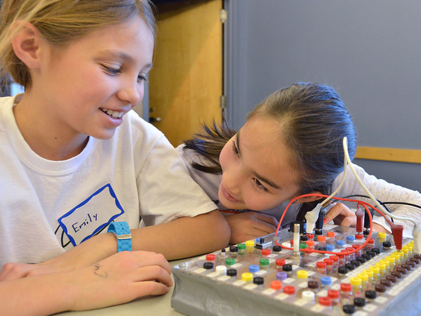 Emily Allen, 10, left,  with Catherine Carmosino, 9, listens for a faint tone from a buzzer on the circuit board during the Electronic Lab taught by Fred Gluck of CU Science Discovery at Mamie Doud Eisenhower Public Library on Saturday.<br /> February 16, 2013<br /> staff photo/ David R. Jennings