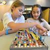 Emily Allen, 10, left, and Catherine Carmosino, 9, try to figure out how to correctly wire a switch on the circuit board during the Electronic Lab taught by Fred Gluck of CU Science Discovery at Mamie Doud Eisenhower Public Library on Saturday.<br /> February 16, 2013<br /> staff photo/ David R. Jennings